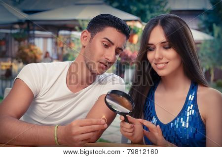 Happy Woman Testing Engagement Ring from Boyfriend with Magnifier