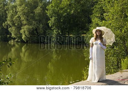 Young woman in white dress near lake