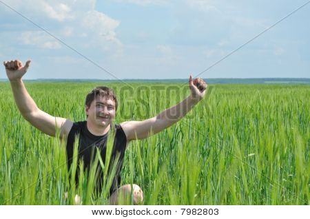 A man sits in a field of green wheat