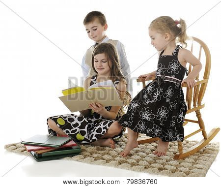 An older elementary girl reading to her younger siblings.  On a white background.