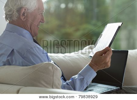 Retired Businessman Analyzing Business Columns