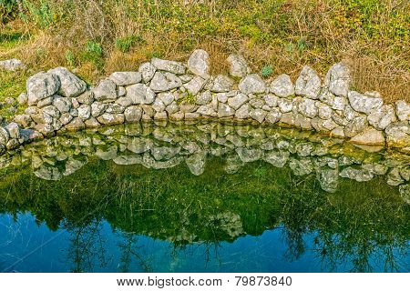 Ancient water trough with surrounding nature reflecting in the water at winter near village Oslje, Croatia. poster