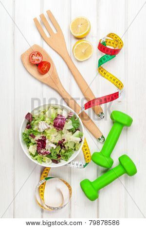 Dumbells, tape measure and healthy food. Fitness and health. View from above over wooden table