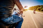 Bikers driving a motorcycle rides along the asphalt road (blurred motion). First-person view. Focus on the dashboard of a motorcycle poster