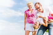 Family romping on field with parents carrying child poster