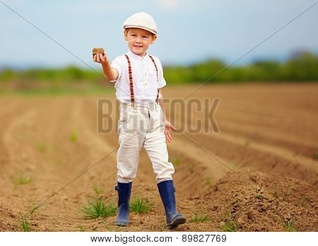 Cute Little Farmer On Spring Field  Holding Earth Clod