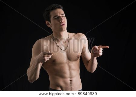 Handsome shirtless young man pointing fingers to a side