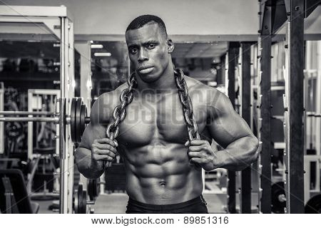 Attractive hunky black male bodybuilder posing with iron chains