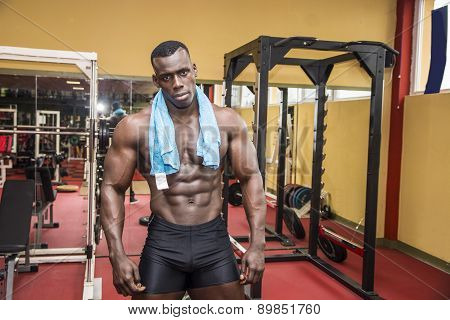 Hunky muscular black bodybuilder working out in gym, resting after exercise poster