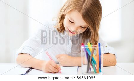 education and school concept - little student girl drawing at school