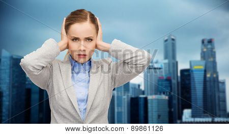 business, emotions, stress, pressure and people concept - stressed businesswoman with covered ears over city background