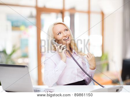 education, business, communication and technology concept - smiling businesswoman or student with laptop computer calling on phone over office room background