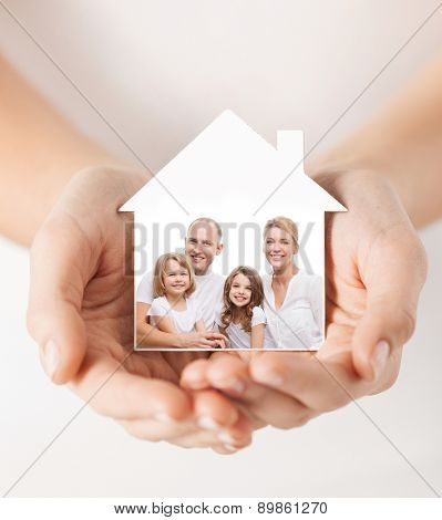 real estate, home insurance and happiness concept - close up of female hands holding white house with happy family picture