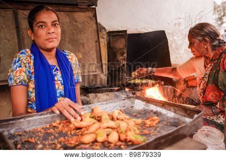 KAMALAPURAM, INDIA - 02 FEBRUARY 2015: Young Indian woman selling fried chilli while her mother makes them in the background