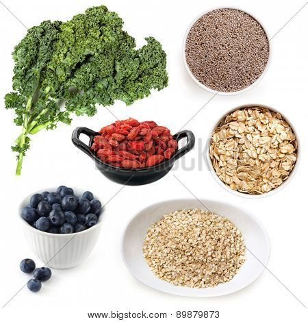 Various superfoods isolated on white.  Includes kale, chia seeds, goji berries, blueberries, oats and quinoa.