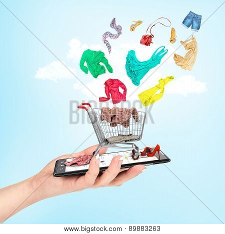 Online Shop Concept. Female Hand Holding A Phone On Which Stands A Shopping Cart With Falling In Her