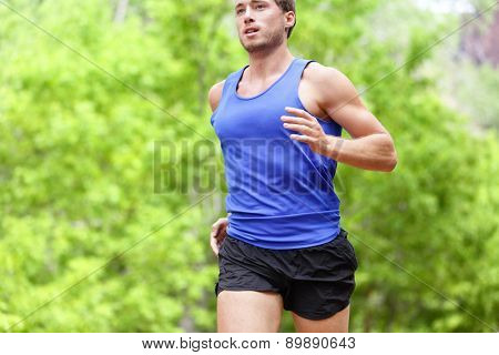 Man running on road. Sport and fitness runner training for marathon run doing high intensity interval training sprint workout outdoors in summer. Male athlete sports model fit and healthy aspirations.