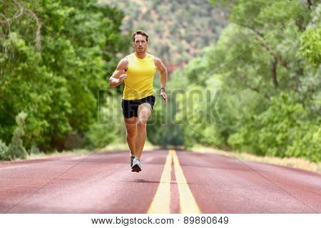 Running man runner sprinting for fitness and health. Male athlete in sprint run wearing sports running shoes and shorts in workout for marathon. Full body length view sprinter running towards camera.