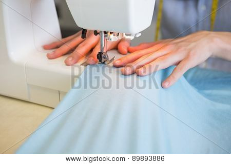 Close up of student using sewing machine at the college