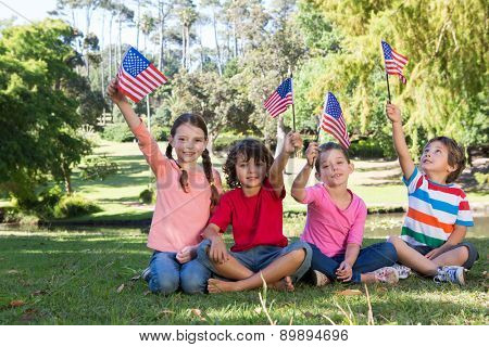 Happy little friends waving american flag on a sunny day