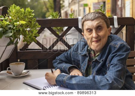 Elderly disabled man with cerebral palsy in outdoor cafe.