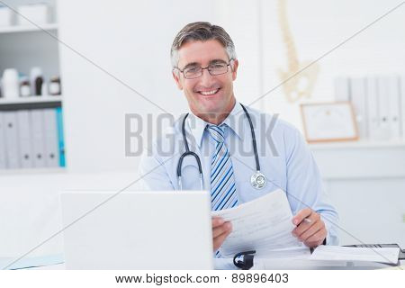 Portrait of male doctor holding document at table in clinic