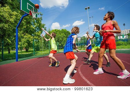 Teenagers in colorful uniforms playing basketball