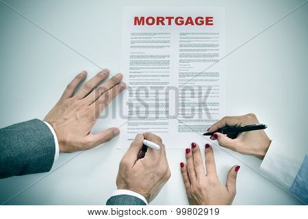 high-angle shot of a man and a woman signing a mortgage loan contract