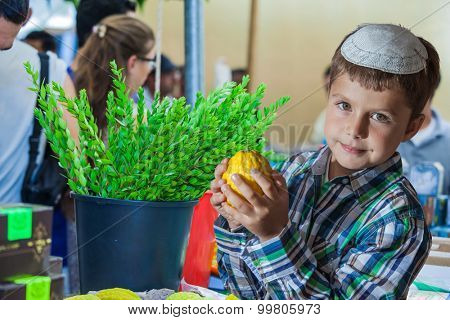 Holiday market in Jerusalem. Seven year old boy in white skullcap with etrog. Ritual plants - myrtle prepared for sale