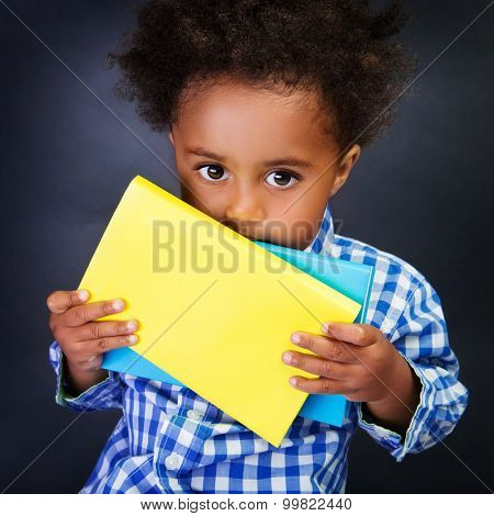 Closeup portrait of cute little shy American schoolboy with textbooks in hands over blackboard background, ready to study in elementary school