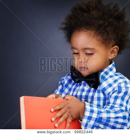 Portrait of serious adorable African schoolboy opening book over dark background, copy space, back to school