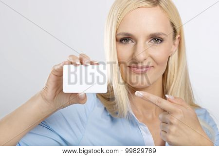 woman holding and pointing to blank card