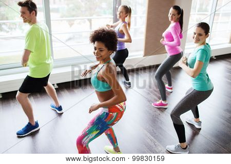 fitness, sport, dance and lifestyle concept - group of smiling people with coach dancing zumba in gym or studio poster