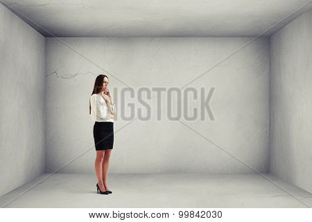 despondent businesswoman thinking about something and looking down in grey empty room