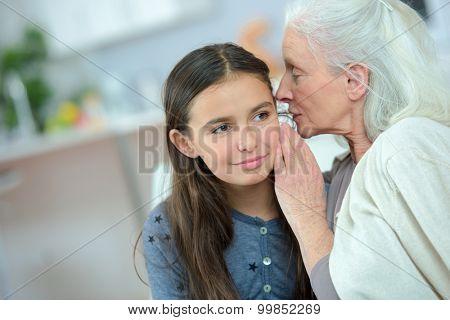Little girl and grandma whispering secrets poster