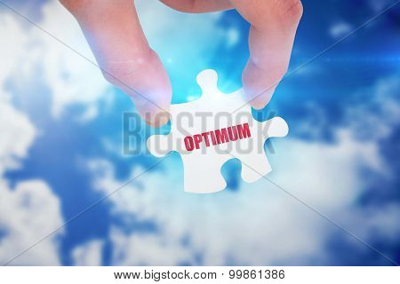 The word optimum and hand holding jigsaw piece against bright blue sky with clouds