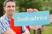 The word seek advice and hand showing card against happy student smiling at camera outside on campus poster