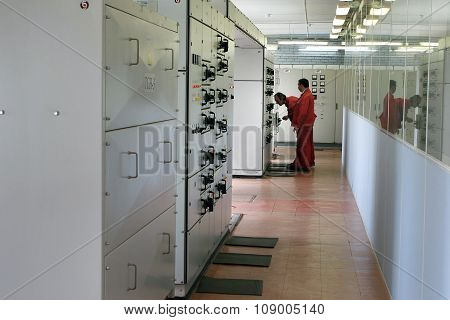 Electricians Inspecting Equipment In The Switchboard Room.