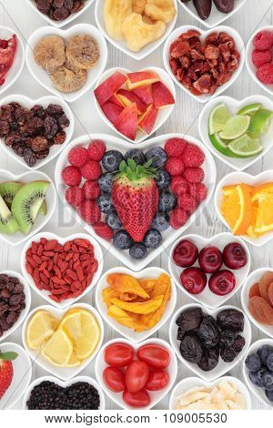 Health and fruit superfood selection in heart shaped porcelain dishes on a wooden distressed background. High in vitamins and antioxidants. poster