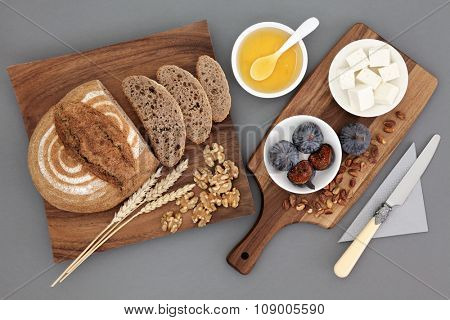 Greek snack food with feta cheese, honey, figs, walnuts and pistachio nuts with rye bread and wheat sheaths on maple wood board over grey background.