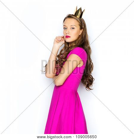 people, holidays and fashion concept - young woman or teen girl in pink dress and princess crown