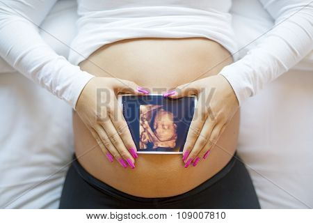 Pregnant woman holds ultrasound photo on the belly in bed