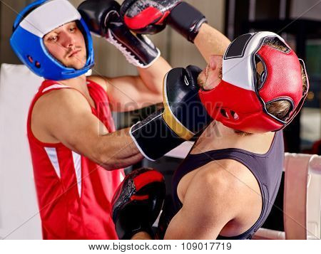 Two  men boxer wearing helmet and  gloves boxing . Uppercut.