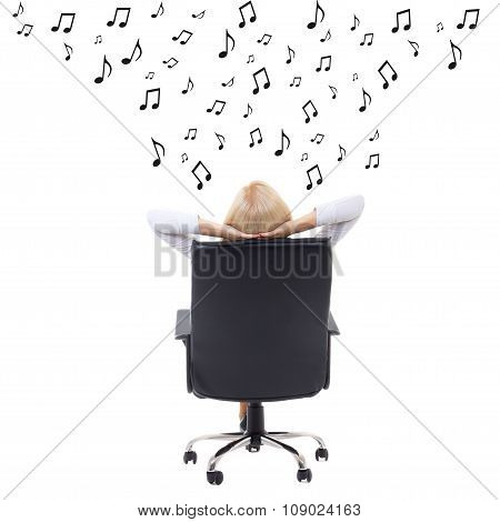 Back View Of Woman With Hands Crossed Behind Her Head Sitting On Office Chair And Listening Music Ov