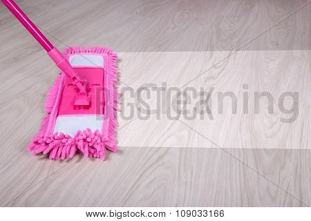 Cleaning Concept - Wet Mop On Wooden Floor With Word Cleaning