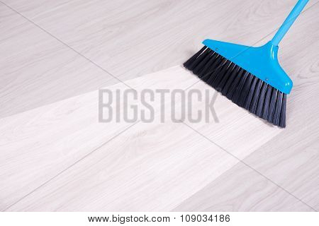 before and aftet cleaning concept - blue broom sweeping parquet floor poster