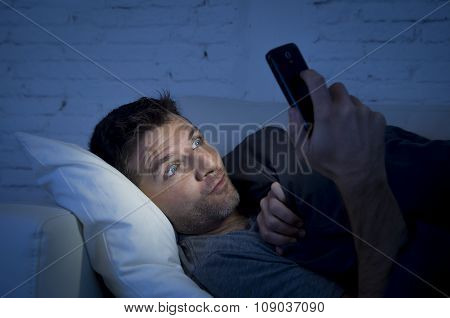 young man in bed couch at home late at night with intense face expression using mobile phone in low light watching online porn enjoying alone in internet addiction poster