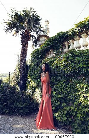 Mulatto Girl Wears Elegant Coral Dress With Bijou ,posing Beside Antic Palace