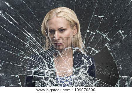 Depressed adult woman stands behind broken glass