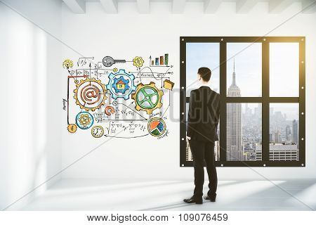 Businessman Looking At The Wall With Business Scheme In Empty Loft Room With Megapolis City View